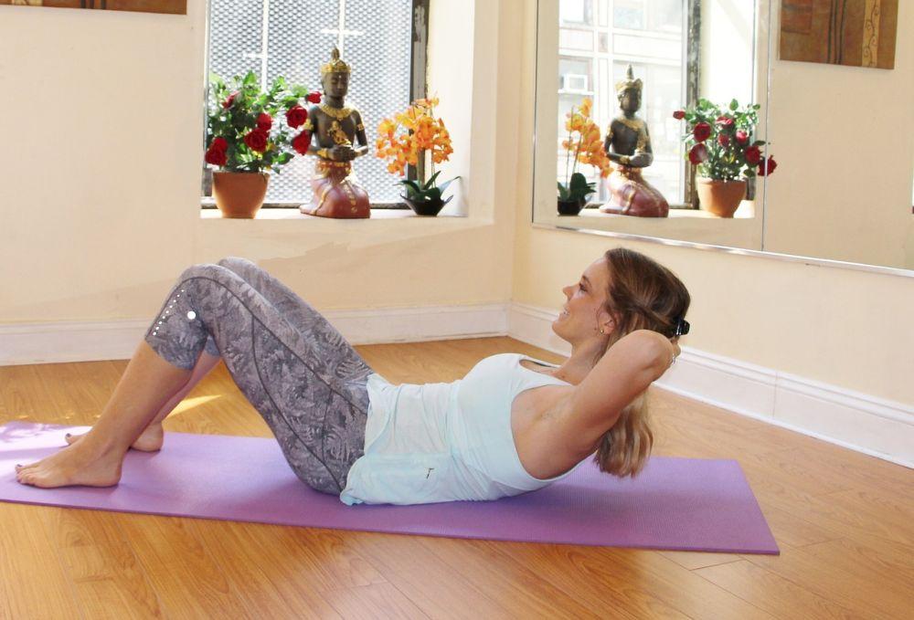 Pilates, una donna fa gli addominali