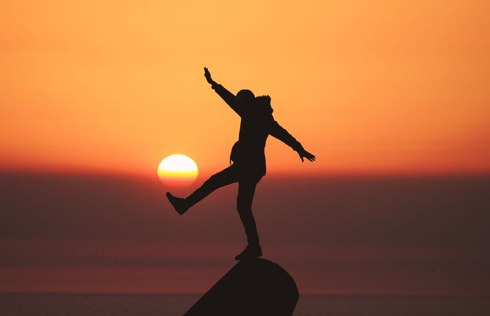 Coraggio, una donna in perfetto equilibrio su una roccia